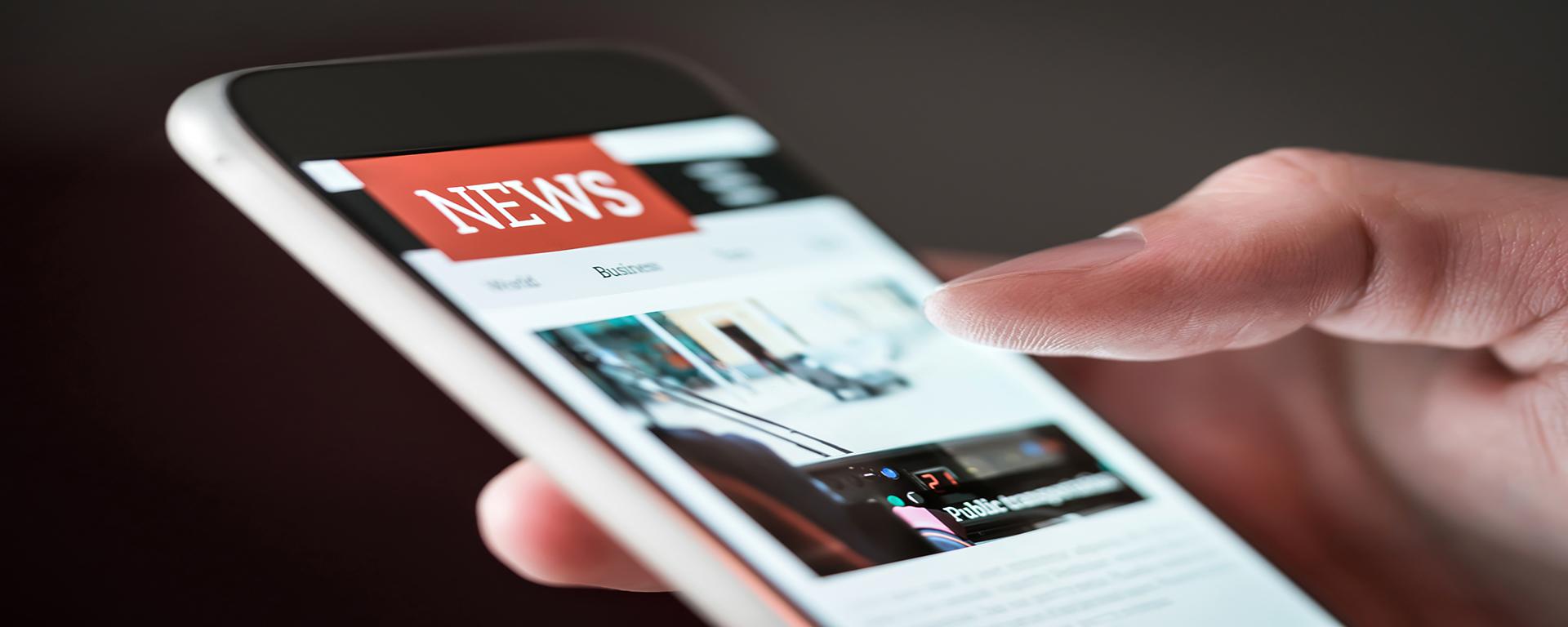 横幅图案:拿着智能手机的手。 智能手机屏幕显示新闻应用程序网站。