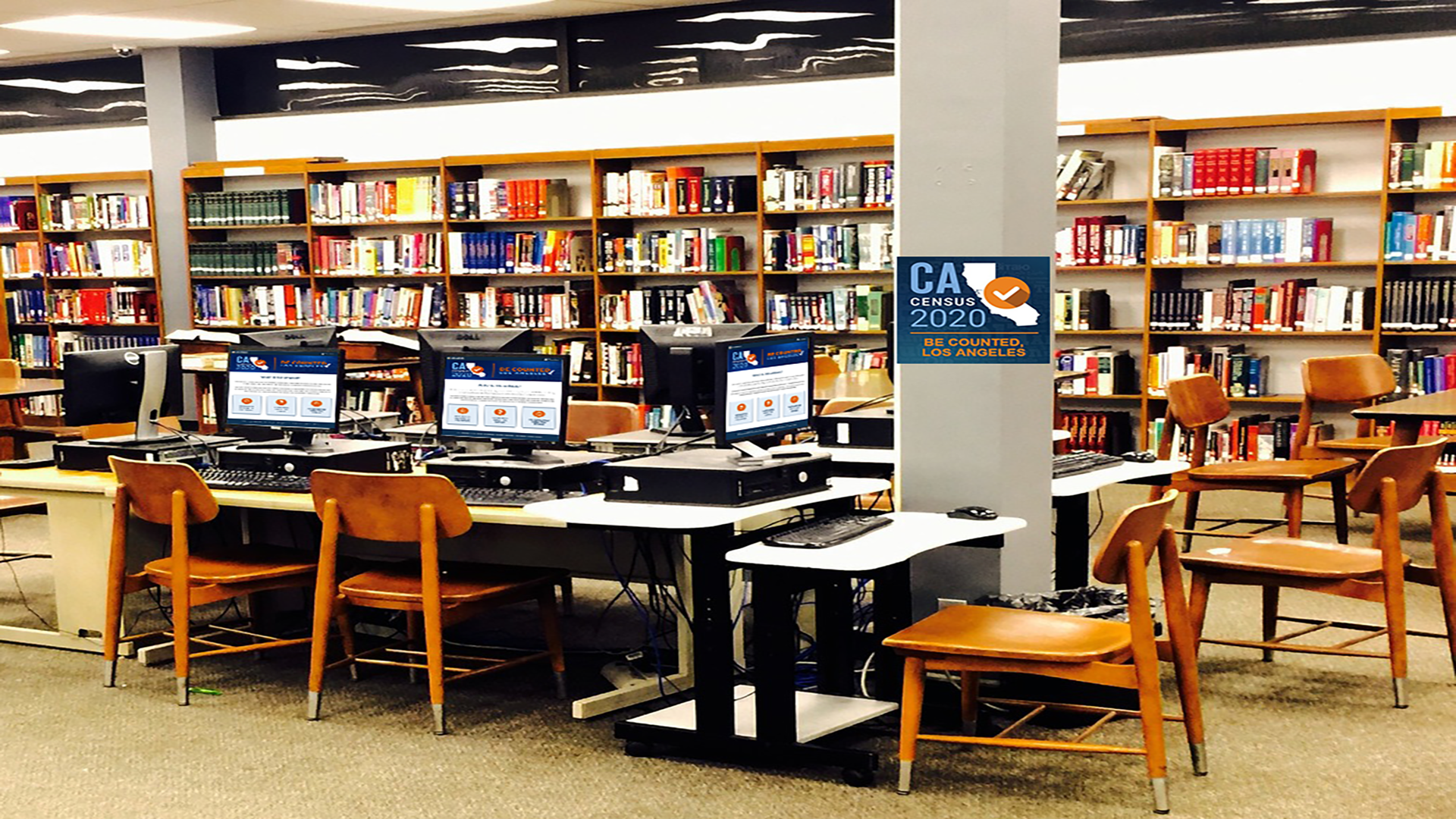 Banner of a library setting with multiple desktop computers displaying images of California Map Logo with text Census 2020 Be Counted Los Angeles.