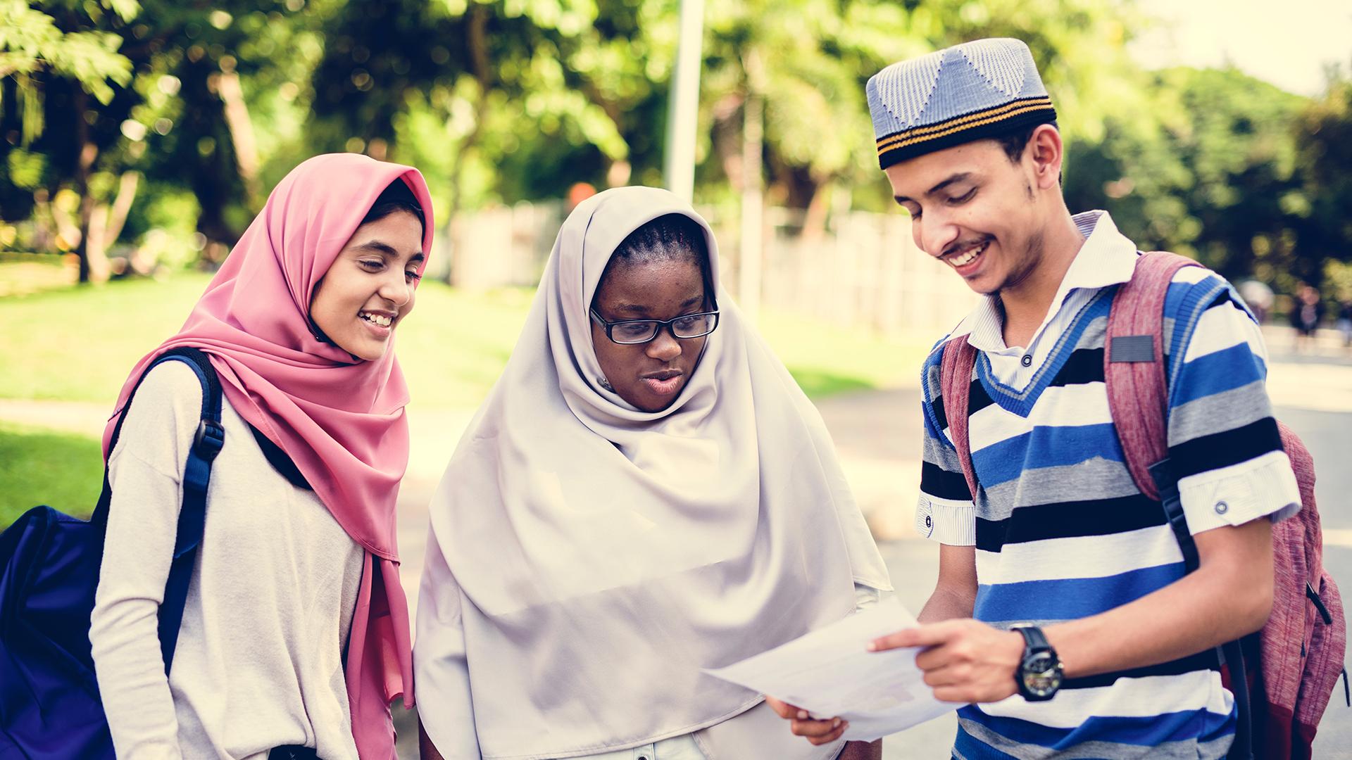 Foto de un grupo diverso de dos mujeres jóvenes con pañuelos en la cabeza y un hombre joven con un sombrero mirando un papel.