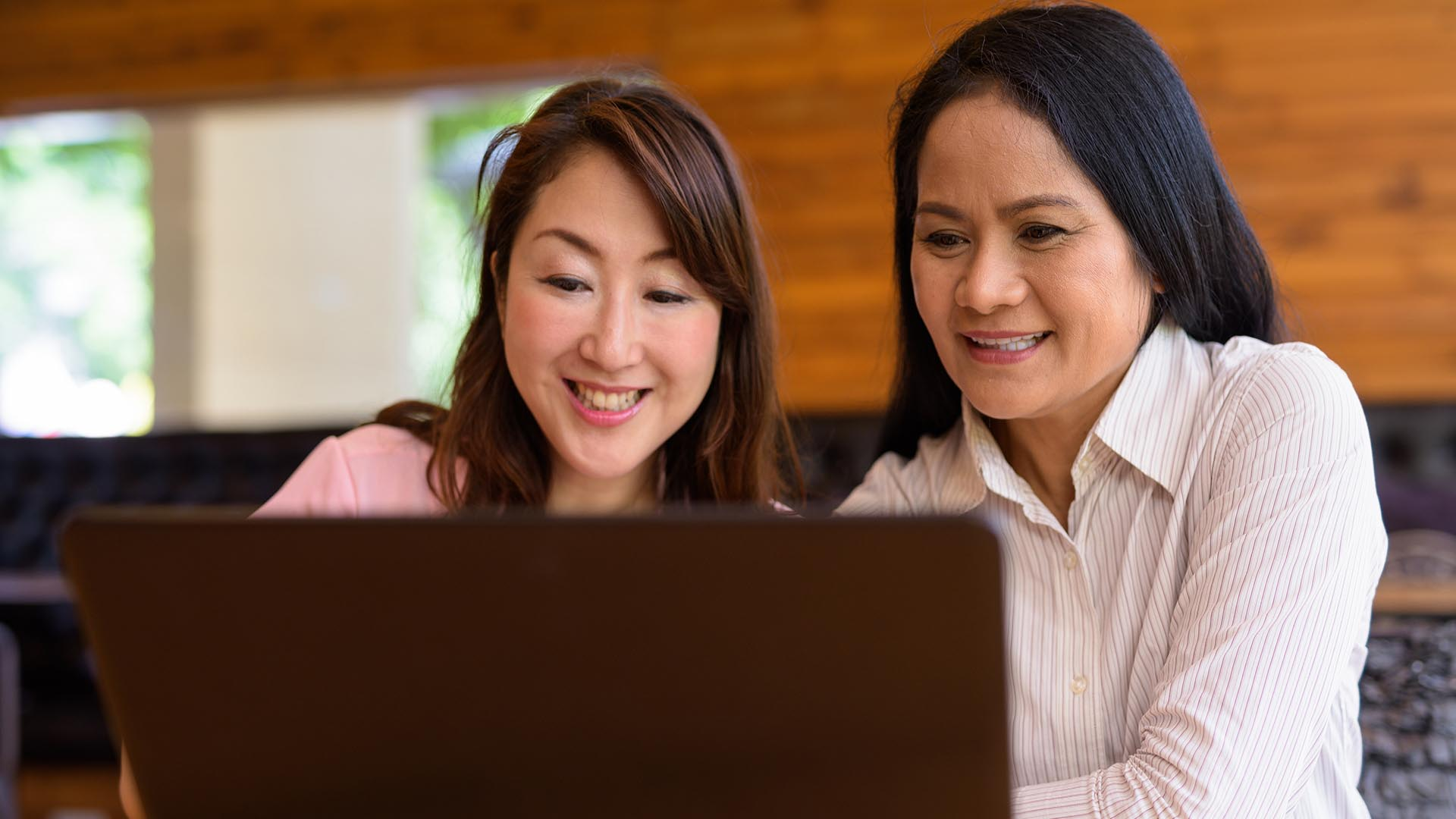 Photo of two women looking at a laptop screen.