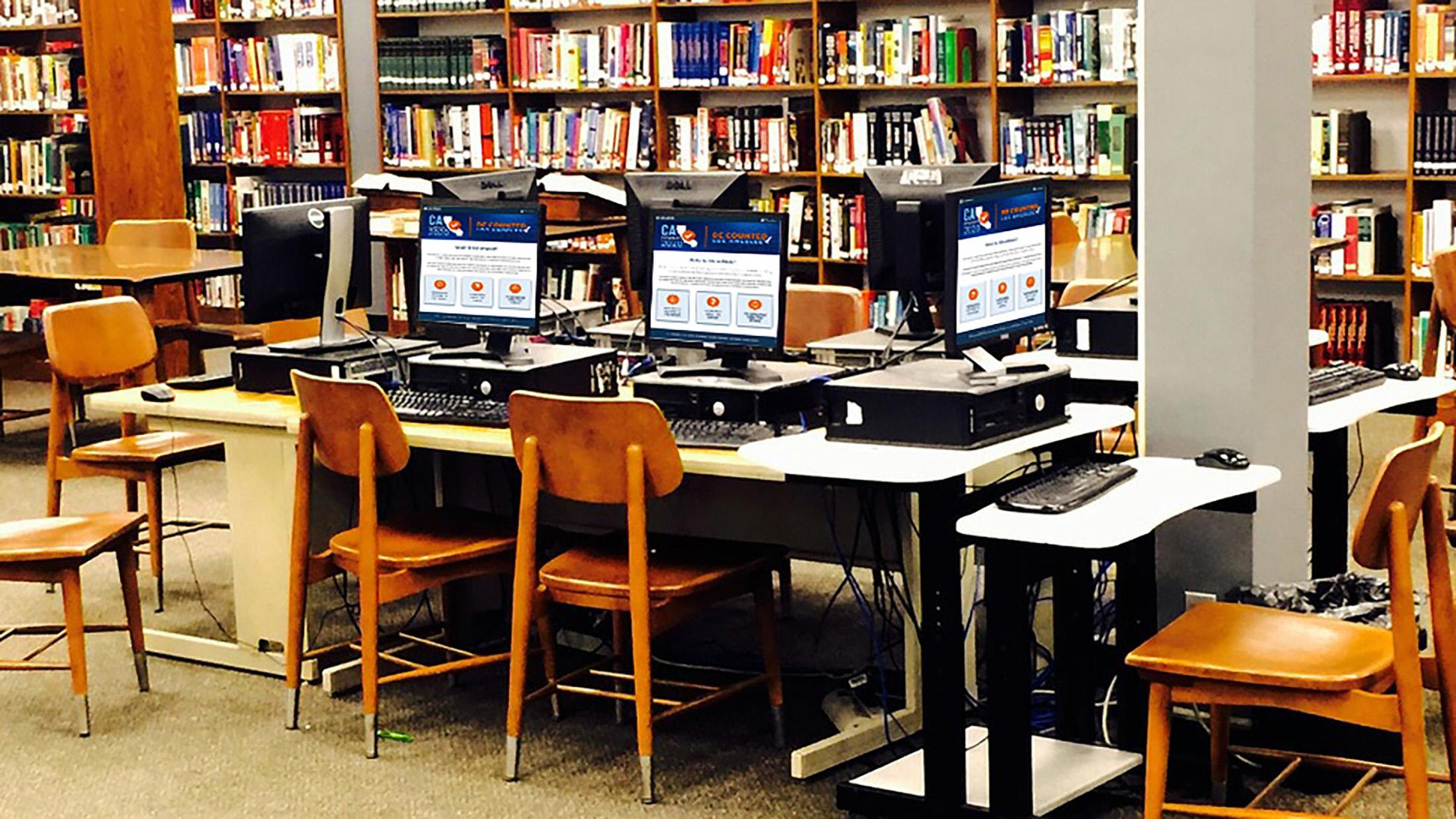 แบนเนอร์รูปพื้นที่ในห้องสมุด มีคอมพิวเตอร์ตั้งโต๊ะหลายเครื่อง บนหน้าจอขึ้นเป็นโลโก้รูปแผนที่รัฐแคลิฟอร์เนีย พร้อมข้อความการจัดทำสำมะโนประชากรในปี 2020 Be Counted Los Angeles