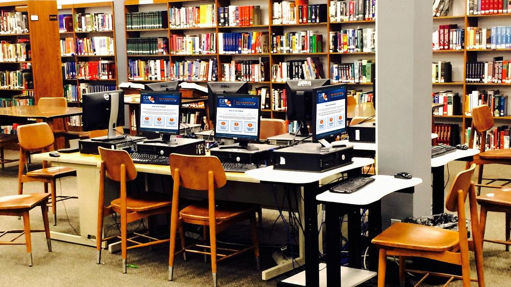 Pancarta de una biblioteca con múltiples computadoras de escritorio que muestran imágenes del logotipo del mapa de California con el texto Censo 2020 Inclúyase en el conteo Los Ángeles.
